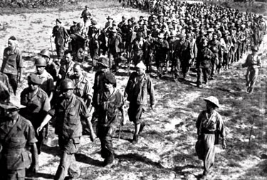 French soldiers march to a prisoner of war camp after they surrendered to the Viet Minh forces after the Battle of Dien Bien Phu