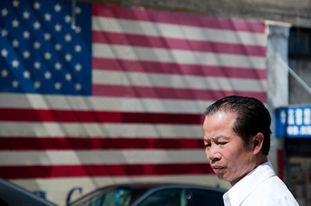 Photo of man of Asian descent in front of American flag